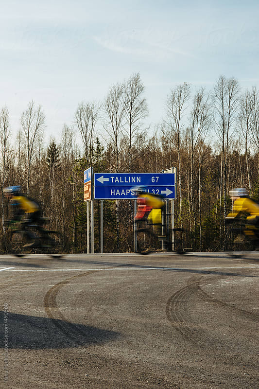 Cyclists driving by a roadsign by Tõnu Tunnel for Stocksy United