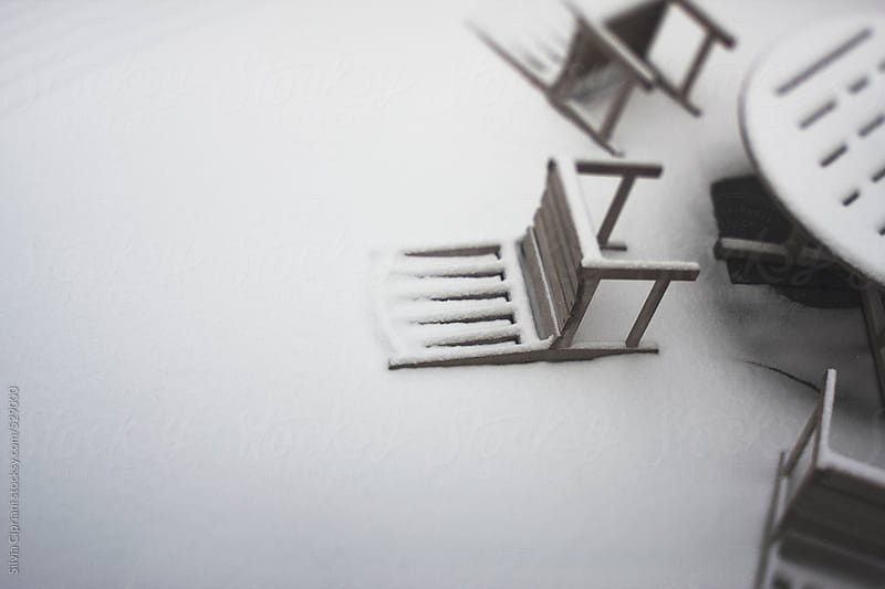 Snow-covered fallen chairs by Silvia Cipriani for Stocksy United