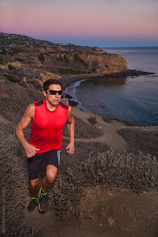 Man running up ocean trail by Neil Kremer for Stocksy United