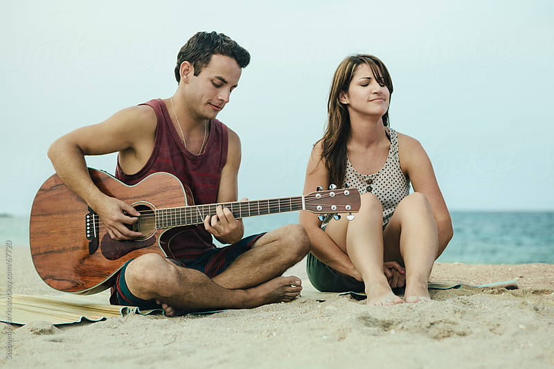 Man Playing Guitar with Woman on the Beach by Stephen Morris for Stocksy United