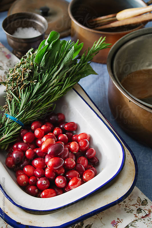 Cranberries and fresh herbs in an old enamel bowl on a kitchen table. Seen from side view  by Darren Muir for Stocksy United