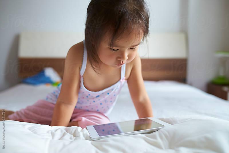 Little girl using tablet indoor by Bo Bo for Stocksy United
