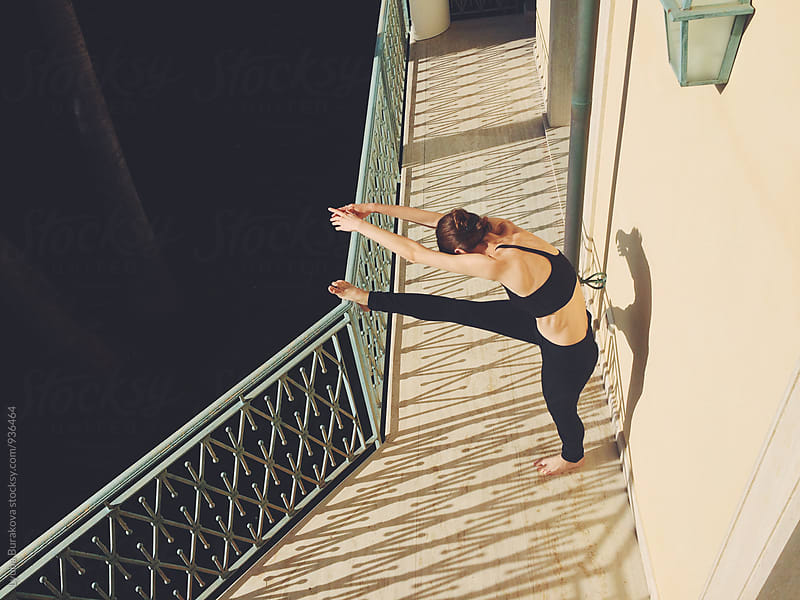 Woman stretching on a balcony by Lyuba Burakova for Stocksy United