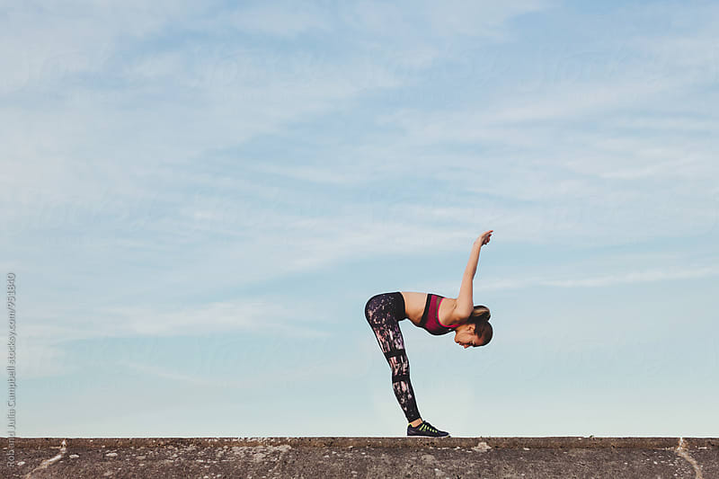 Young, healthy caucasian woman stretching before running outisde by Rob and Julia Campbell for Stocksy United