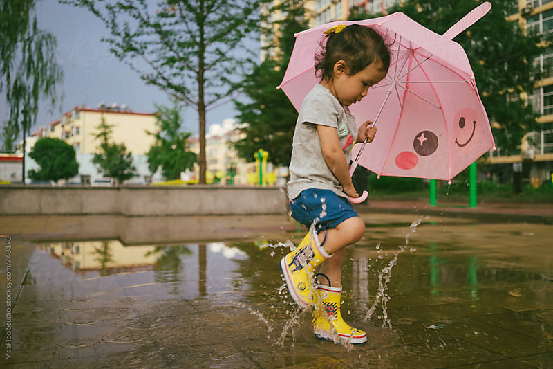 Baby girl Girl wearing rubber boots and jumping in rain puddle by Maa Hoo for Stocksy United