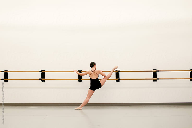 A young woman stretching her legs on ballet bars by Jennifer Brister for Stocksy United