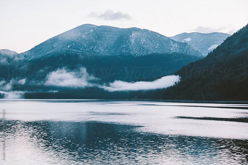 Low clouds over a mountain lake by Justin Mullet for Stocksy United