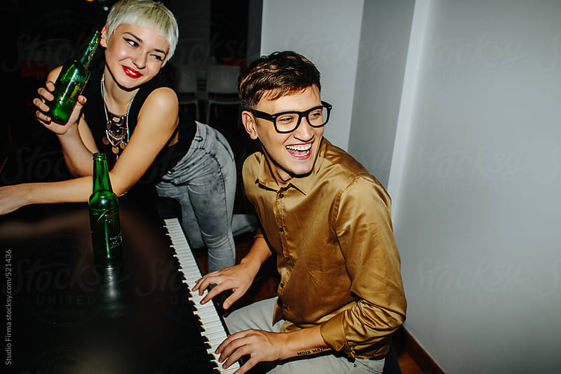 Young couple having fun with piano. by Studio Firma for Stocksy United