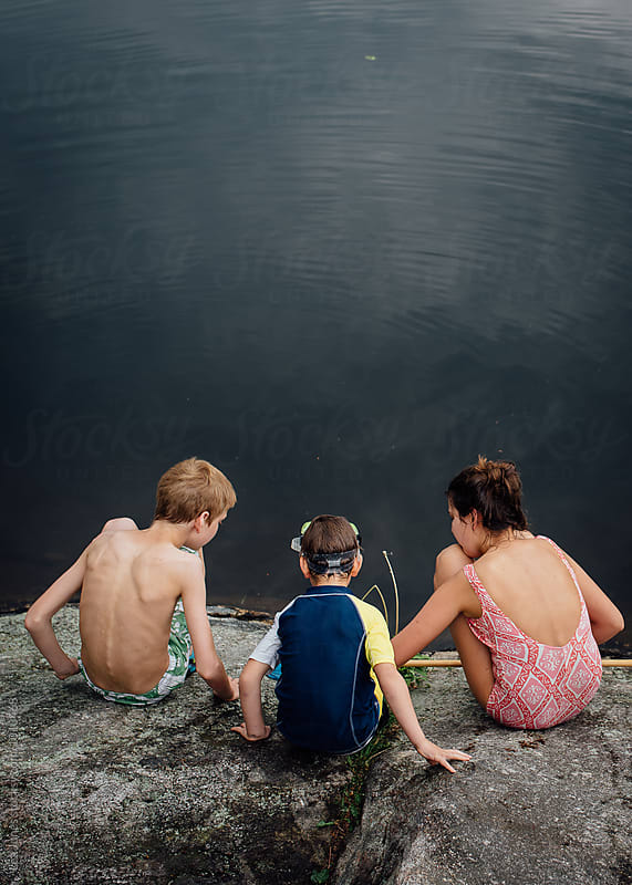 kids sitting by a lake by Léa Jones for Stocksy United