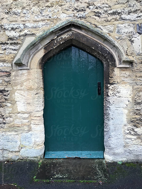 Old dark green arched door set in a stone building. by Paul Phillips for Stocksy United