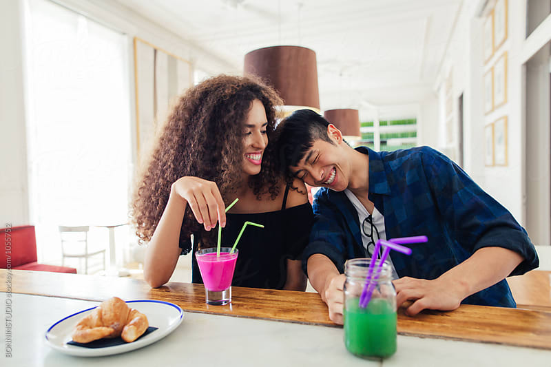 Cool couple having fun while drinking fresh smoothies in a restaurant. by BONNINSTUDIO for Stocksy United