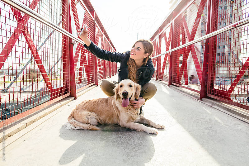 Woman on a bridge taking a selfie with her dog. by BONNINSTUDIO for Stocksy United