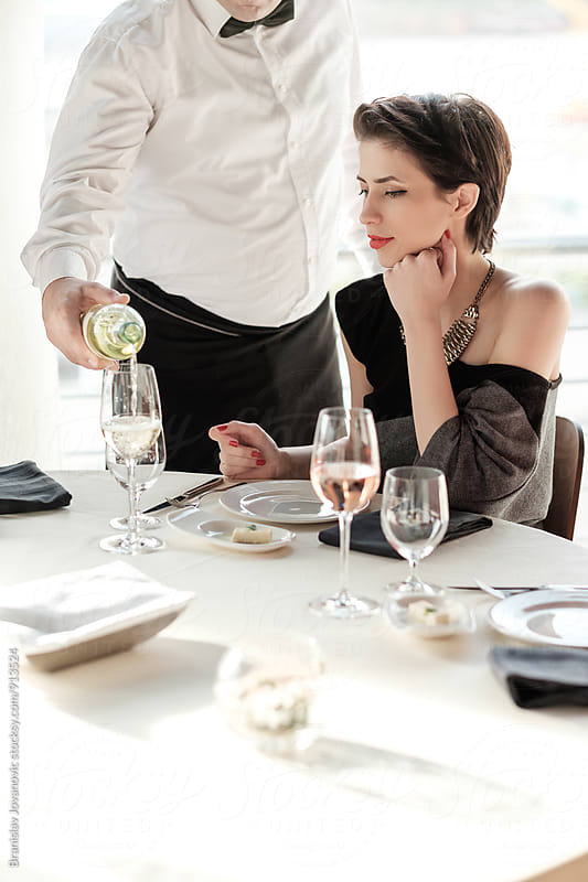 Woman Sitting at the Table in the Restaurant while Waiter is Pouring Wine in the Glass by Brkati Krokodil for Stocksy United