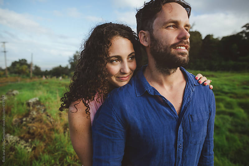Young, romantic couple standing together outside smiling and cuddling in nature by Rob and Julia Campbell for Stocksy United