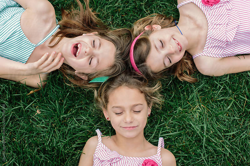 Three young sister laying on grass with their heads together by Jakob for Stocksy United