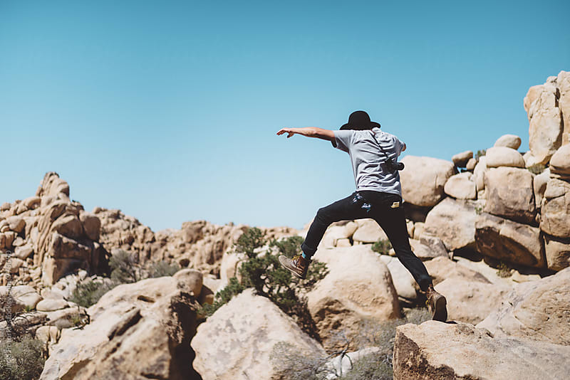 Young man jumping on rocks by Jacki Potorke for Stocksy United