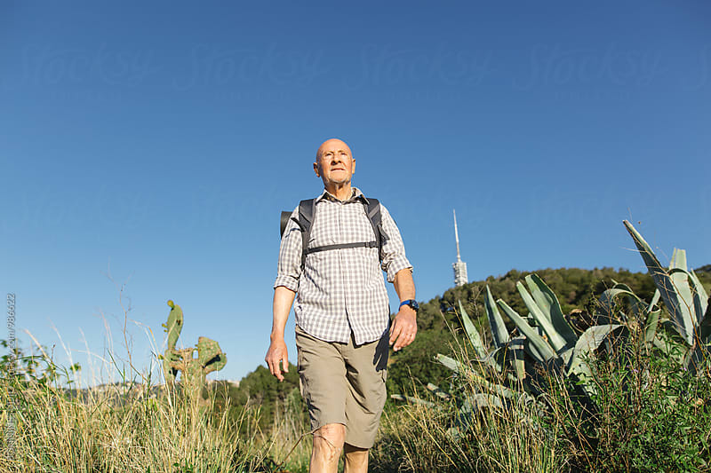 Senior man hiking in a mountain trail under a blue sky. by BONNINSTUDIO for Stocksy United