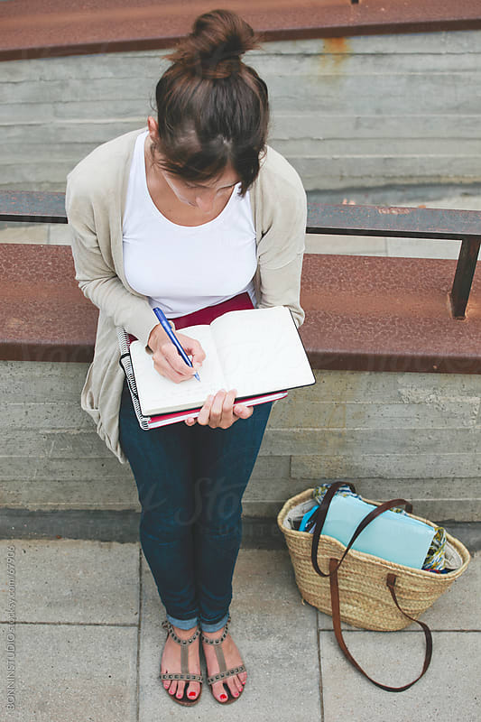 Beautiful casual young student woman writing on notebook on the street. by BONNINSTUDIO for Stocksy United