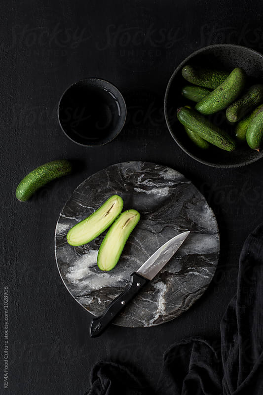 Cocktail avocado on a cut board  by KEMA Food Culture for Stocksy United