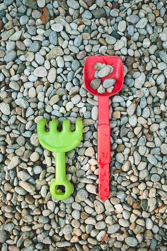 Pair of plastic shovel toys on rocks background. by BONNINSTUDIO for Stocksy United