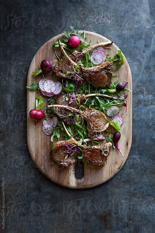 Pan seared lamb cutlets  with radish and arugula garnish by Nadine Greeff for Stocksy United