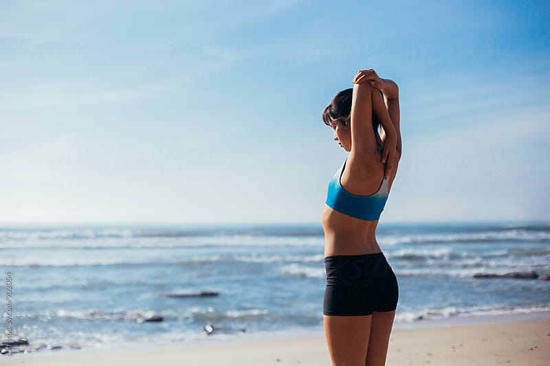 Female athlete concentrating on stretching at the beach by paff for Stocksy United