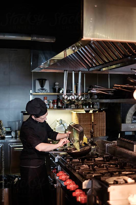Female Cook Preparing  Meal in the Restaurant Kitchen by Branislav Jovanović for Stocksy United