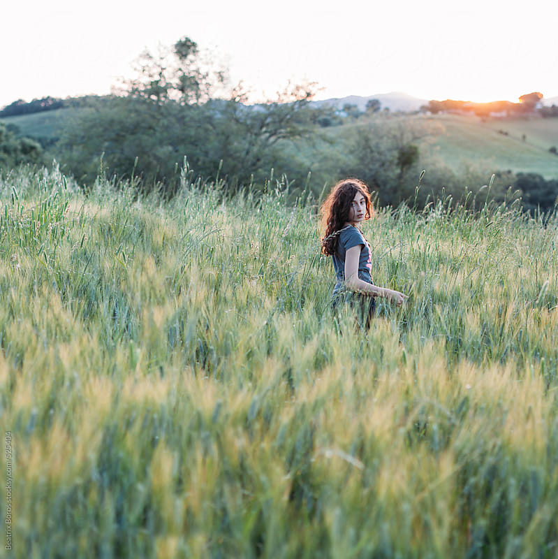 Girl turning back in a countryside field at Sunset by Beatrix Boros for Stocksy United