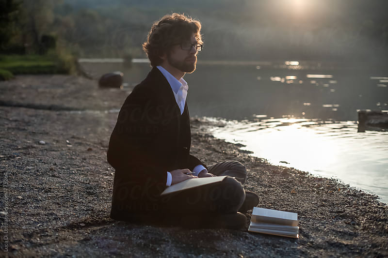 Young man, sitting cross-legs on a beach by a lake, looking far, getting inspired for writing. by Luca Di Lotti for Stocksy United