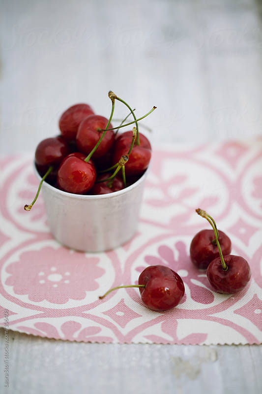 Bunch of red cherries in enamel tan on flowered cloth by Laura Stolfi for Stocksy United