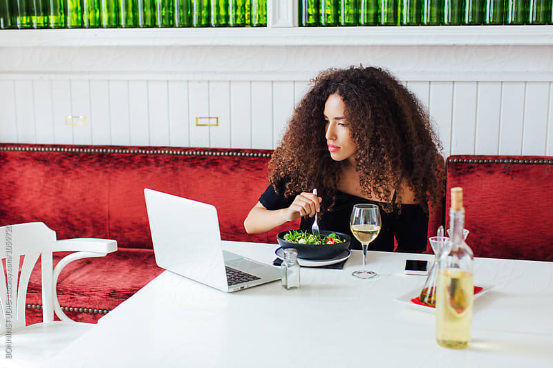Curly woman working with her laptop whilst eating in a cool restaurant.  by BONNINSTUDIO for Stocksy United