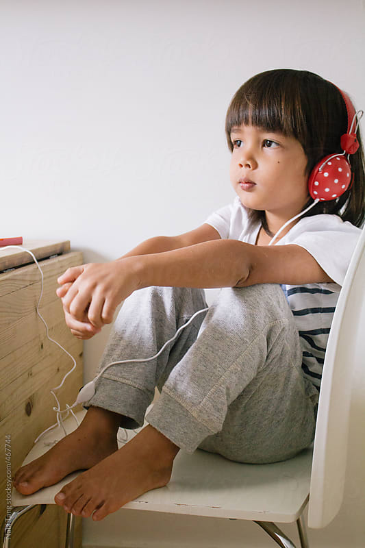 Adorable little asian boy sitting alone on the chair listening to the music by Nabi Tang for Stocksy United