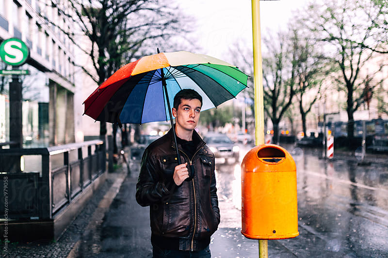 Teenager with umbrella on bus stop, urban Berlin by Michael Zwahlen for Stocksy United