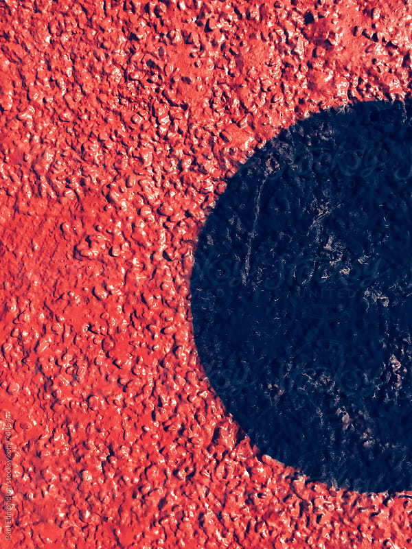 Circular painted shapes on bright red wall, close up by Paul Edmondson for Stocksy United