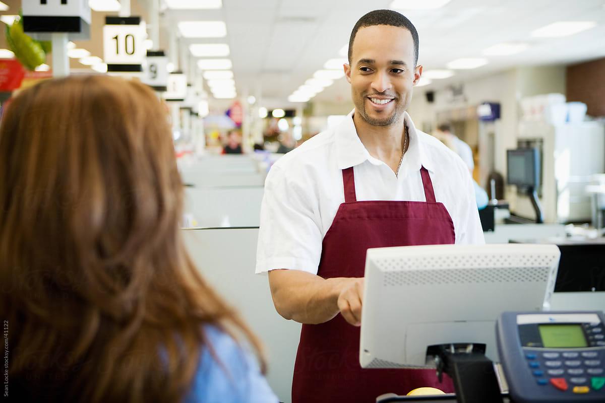 Supermarket: Cheerful Cashier In Supermarket by Sean Locke