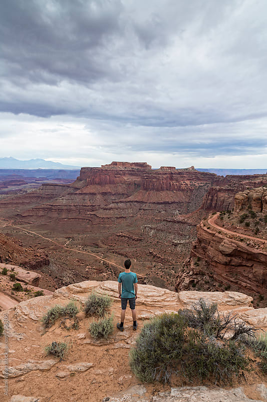 Teenage boy standing on the edge of a cliff, looking out over Canyonlands National Park Utah by Adam Nixon for Stocksy United