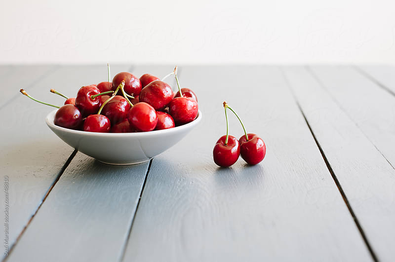 A bowl of ripe red cherries on a grey table by Suzi Marshall for Stocksy United