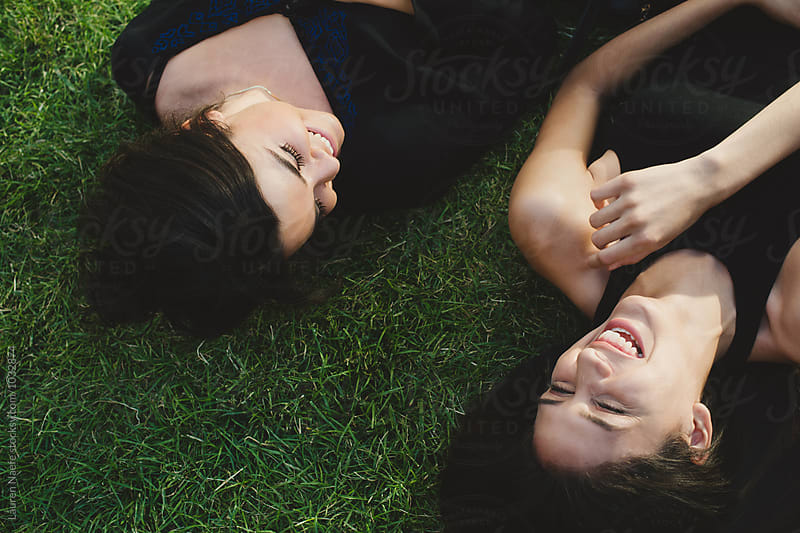 Friends lying in the grass and laughing by Lauren Naefe for Stocksy United