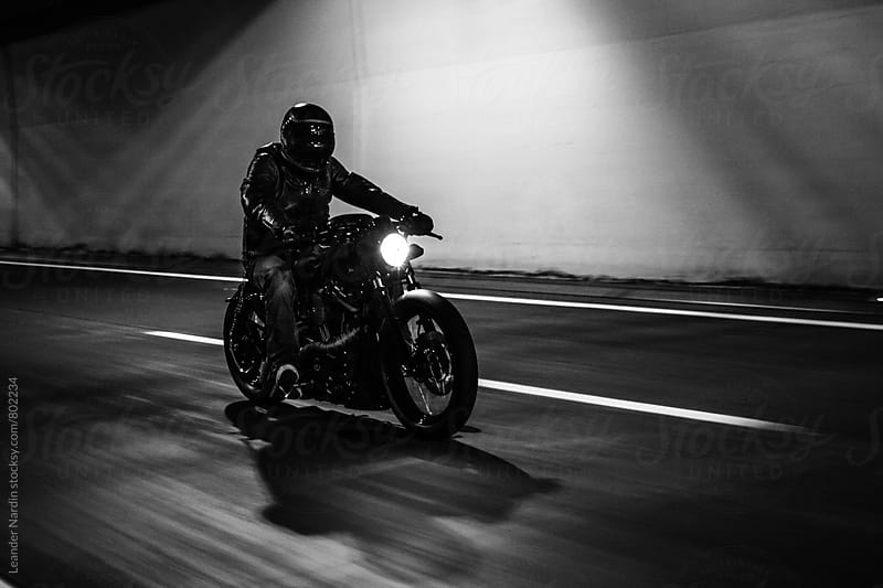 dark rider riding his bike fast in a tunnel - black and white by Leander Nardin for Stocksy United