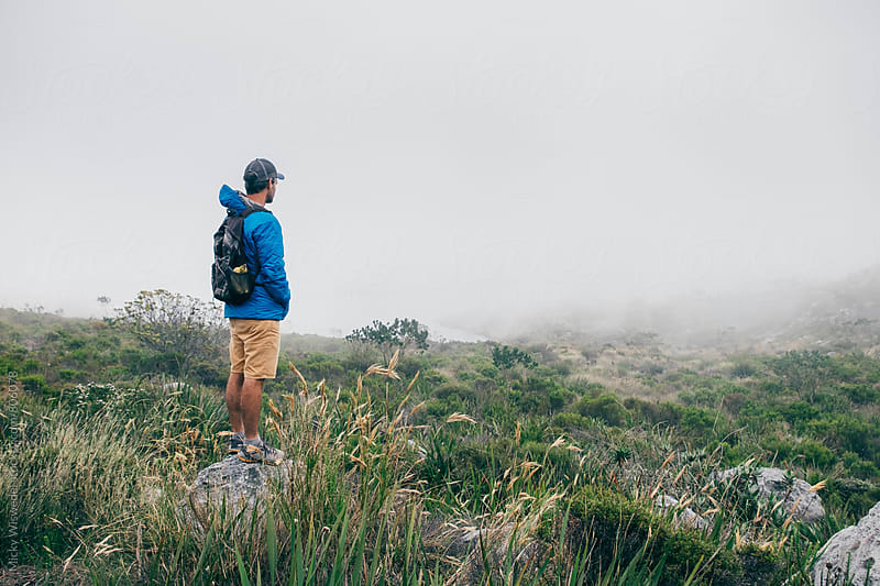 Hiker standing on a misty mountain top by Micky Wiswedel for Stocksy United