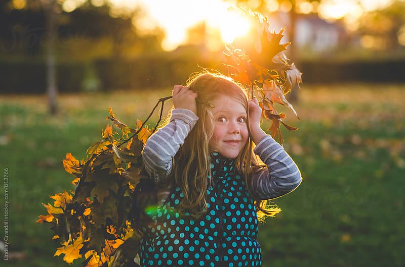 Girl playing with leaves by Lindsay Crandall for Stocksy United