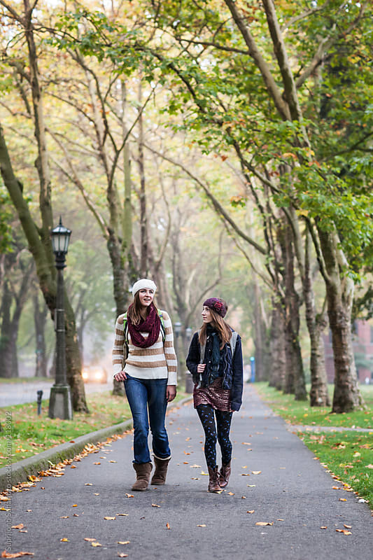 Two female college students walking on campus by Suprijono Suharjoto for Stocksy United
