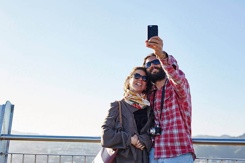 Couple taking selfie by Martí Sans for Stocksy United