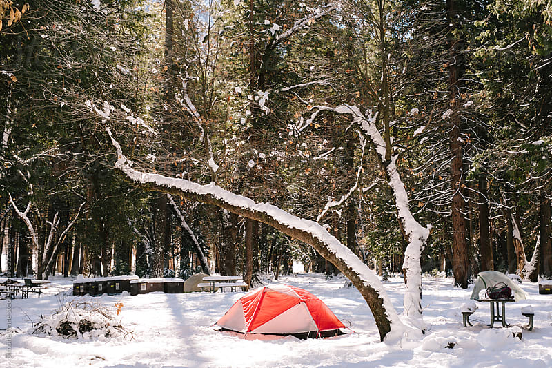 Orange and white tent in the snow by Simone Anne for Stocksy United