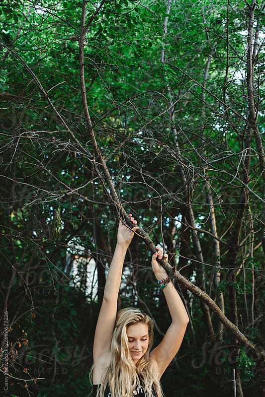 Pretty girl holding on to branch by Carey Shaw for Stocksy United