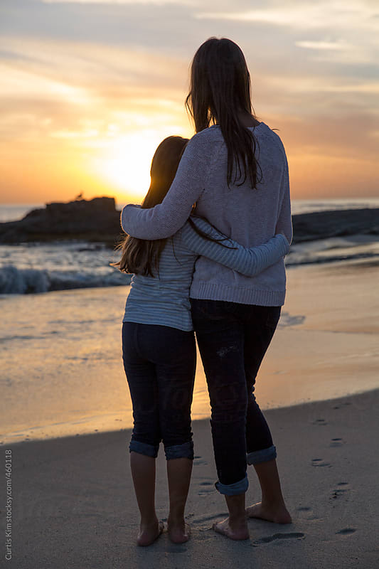 Two girls holding each other enjoying the sunset at the beach by Curtis Kim for Stocksy United