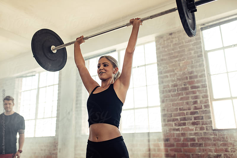 Muscular woman lifting a barbell in gym by Jacob Ammentorp Lund for Stocksy United
