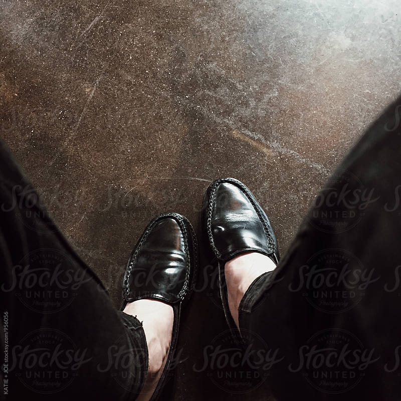black loafers shoes with black pants on a dark floor by KATIE + JOE for Stocksy United
