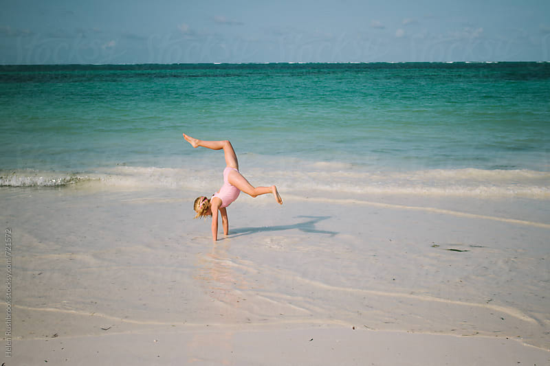 A little girl practising her handstands on a beach by Helen Rushbrook for Stocksy United