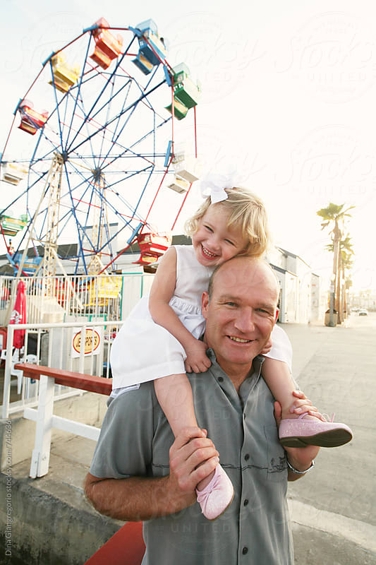 Father and Daughter near Ferris Wheel and Carnival by Dina Giangregorio for Stocksy United